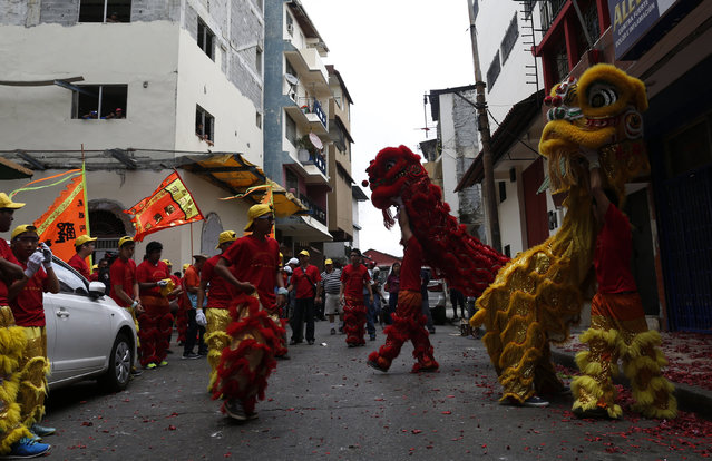 Dancers perform a lion dance outside a local shop during celebrations of the Chinese Lunar New Year