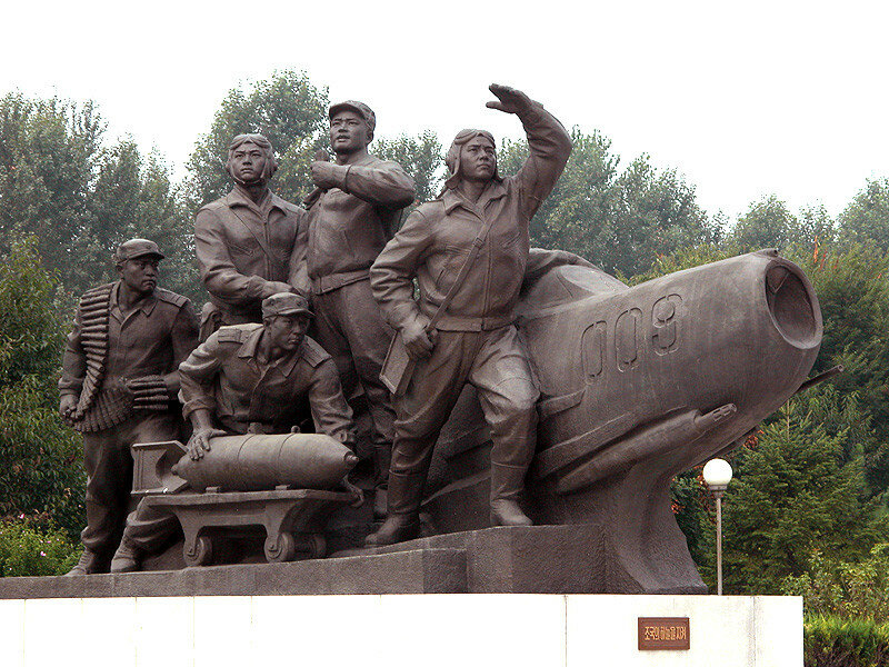 A monument in Pyongyang, depicting North Korean airmen and a MiG fighter.jpg