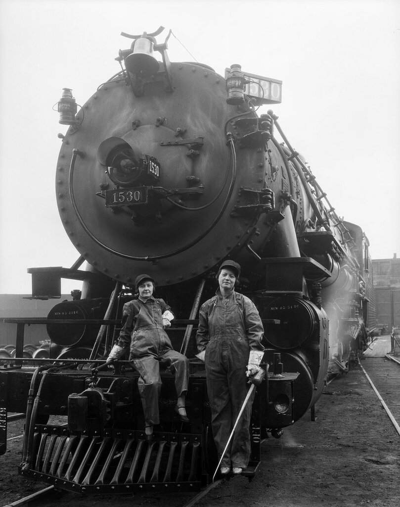 D&RGW locomotive 1530 is at Burnham Shops, Denver, Colorado. Women in bib overalls and gloves pose, one holds an oilcan. April, 1926.jpg