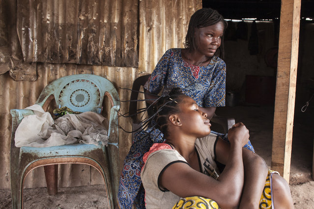 Lydie Ouilibozoumna, 25, braids the hair of Sibel Malipoukayade, 23, in M'Poko Internally Displ