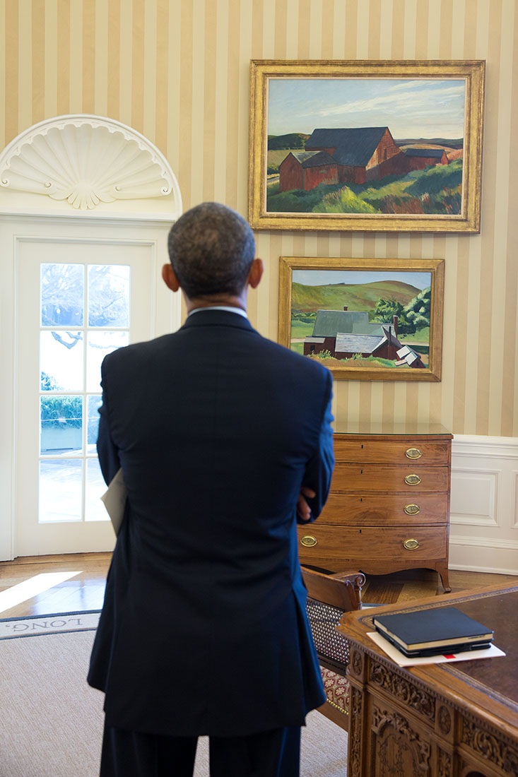 President Barack Obama looks at  the Edward Hopper paintings now displayed in the Oval Office, Feb. 7, 2014.  The paints are Cobb's Barns, South Truro, top, and Burly Cobb's House, South Truro. (Official White House