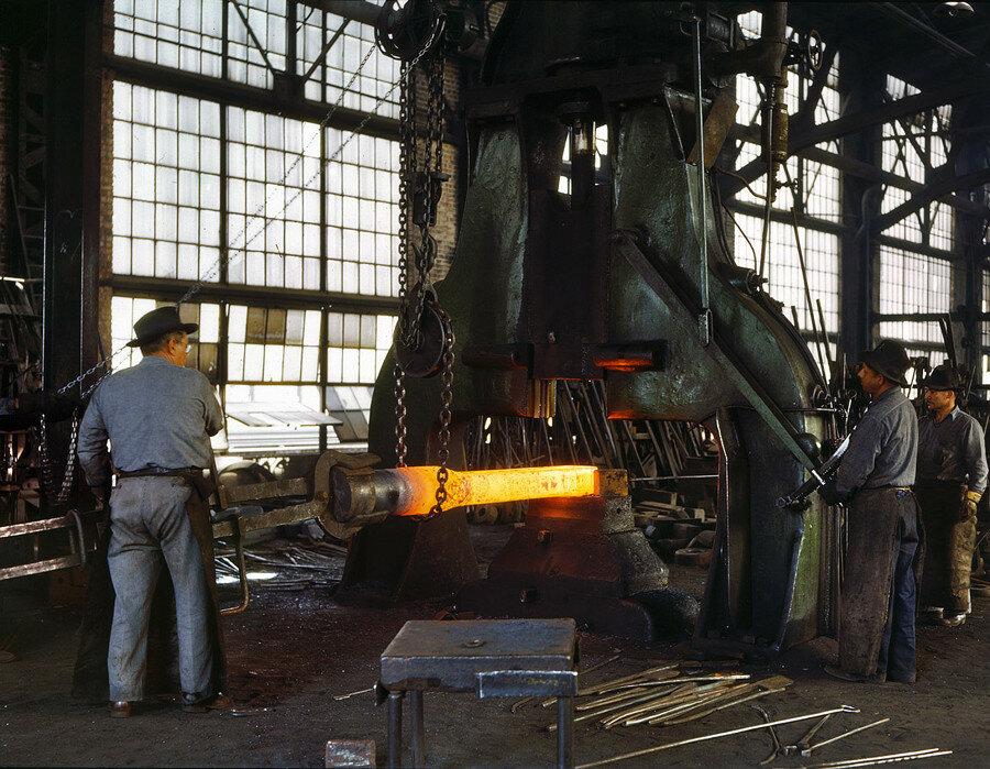"March 1943. ""Santa Fe R.R. shops, Albuquerque. Hammering out a drawbar on the steam drop hammer in the blacksmith shop."".jpg"