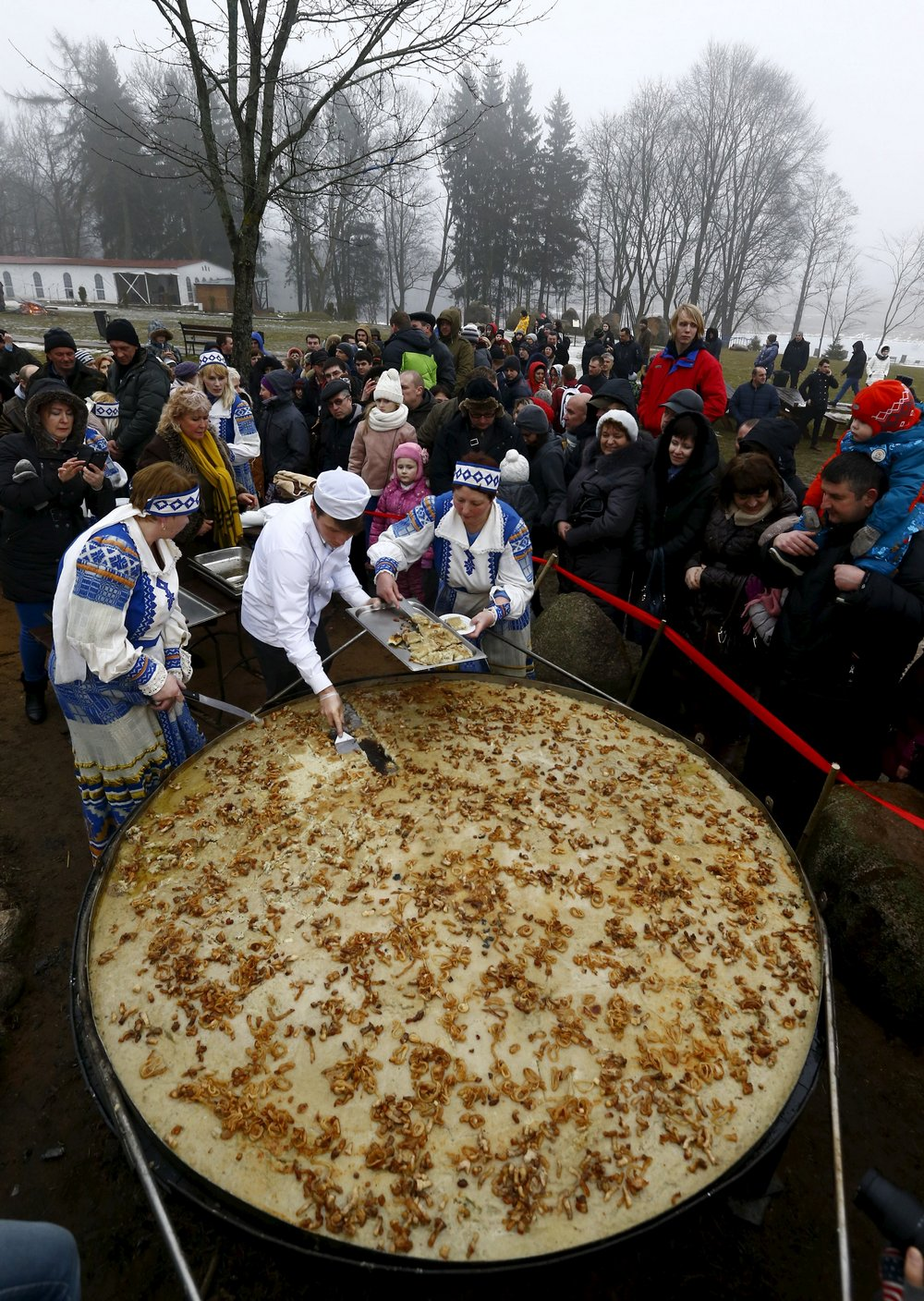 Employees cut fried dranik, a potato pancake that is the national dish of Belarus, to entertain visitors in the Sula History Park near the village of Sula