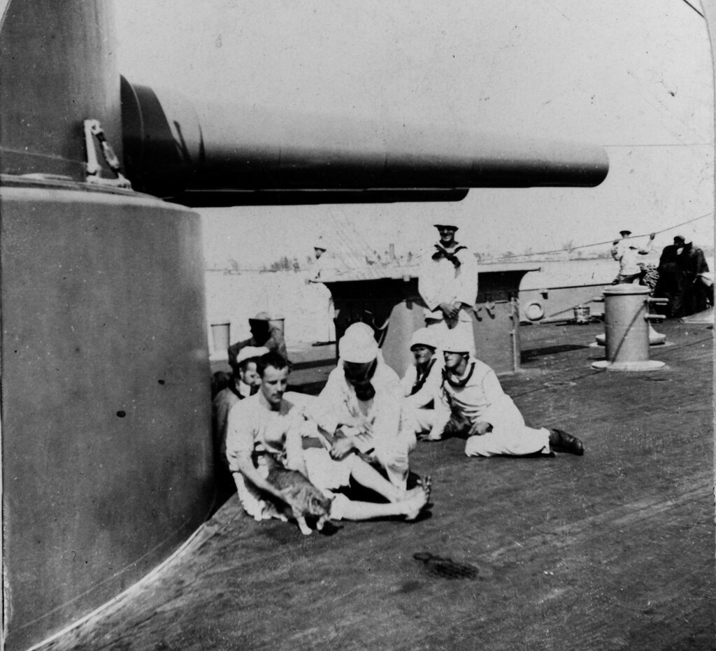 USS PURITAN (BM-1) Crewmen relaxing by her after 12'' turret, 1898. Note cat.