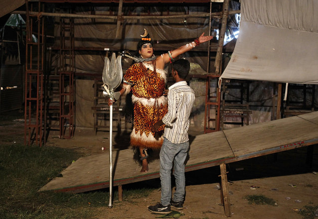 An artist dressed as Shiva gestures as he gets ready backstage before performing during the ten-day