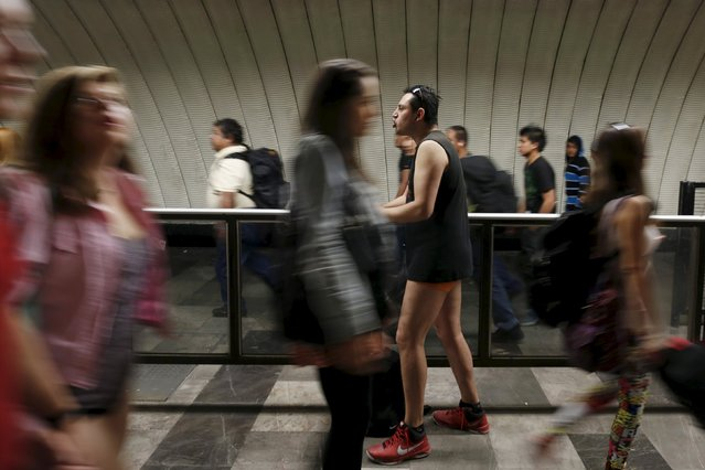 "A passenger stands without pants inside the subway as people walk pass during the ""No Pants Subway R"