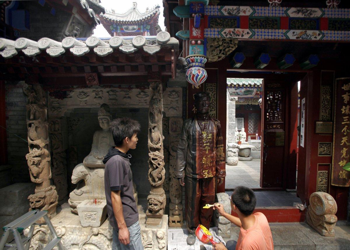 Ассистенты помогают Болину слиться со стеной старого храма в Пекине.