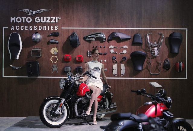 A model poses on a Moto Guzzi motorcycle displayed at the Indian Auto Expo in Greater Noida, on the