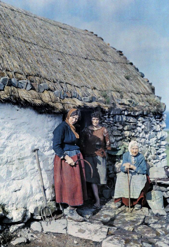 Три поколения крестьянок стоят возле своего каменного дома.