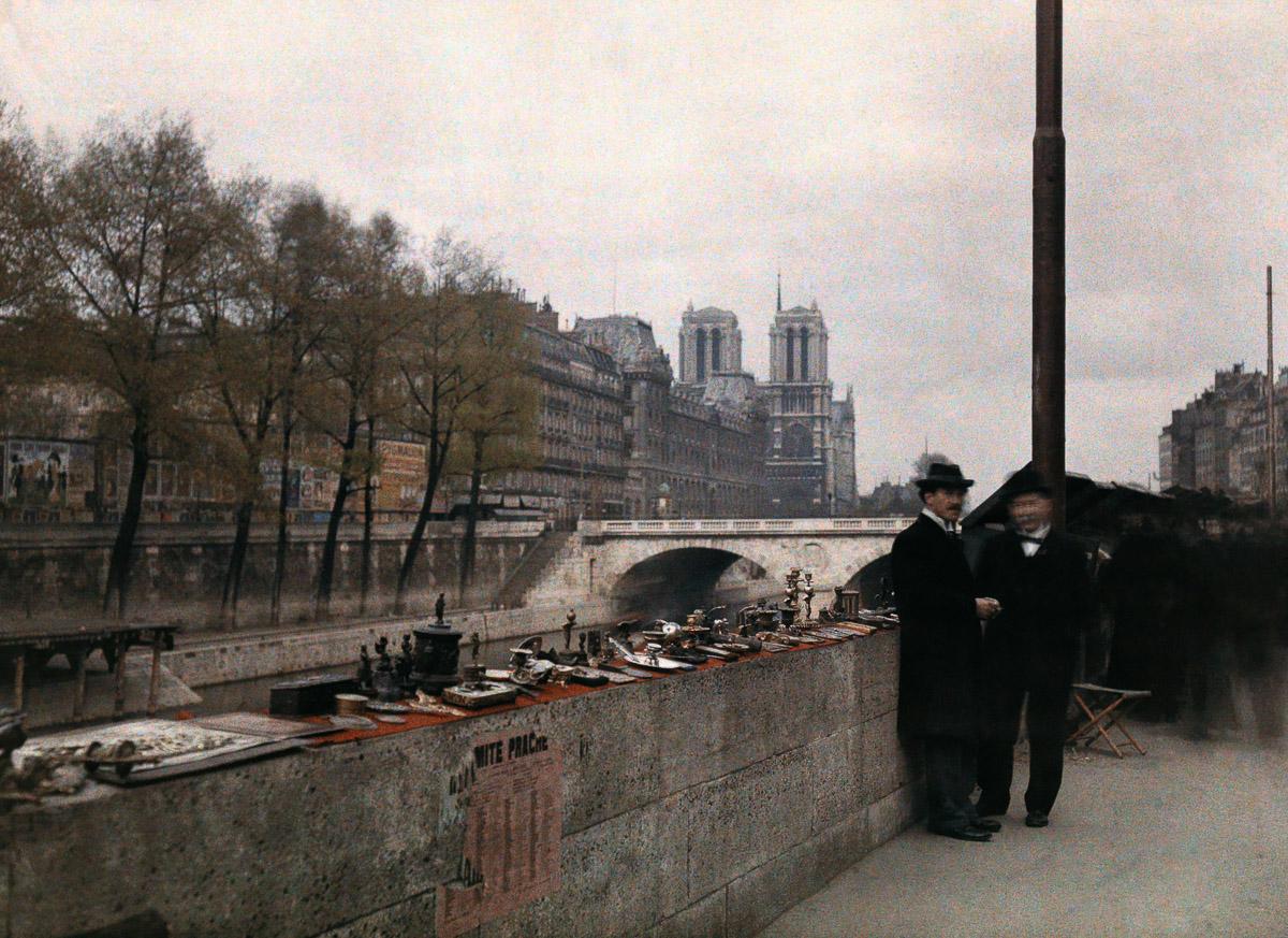Мужчины стоят рядом с выставленными на продажу предметами недалеко от собора Парижской Богоматери.