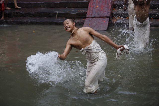 A devotee splashes water towards other devotees after taking a holy bath at Pashupatinath Temple dur
