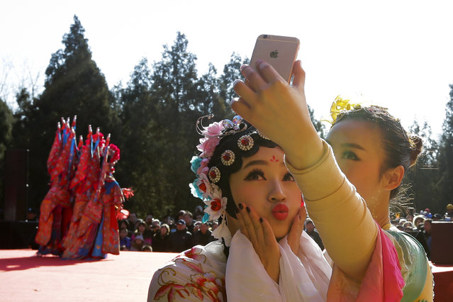 Chinese dancers dressed in traditional costume take a selfie in backstage during a temple fair for a