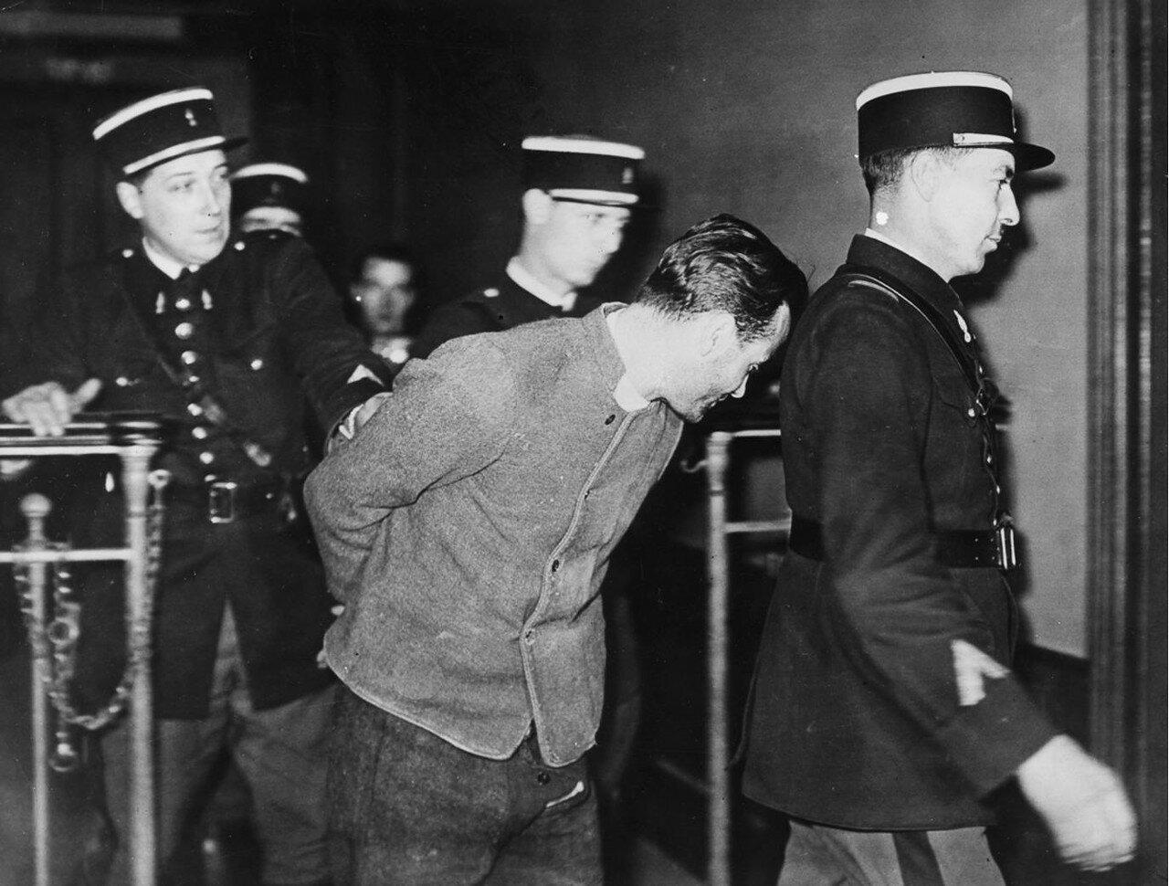 16. Вейдмана уводят в наручниках после его захвата полицией