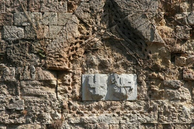 Старинные гербы на стене крепости