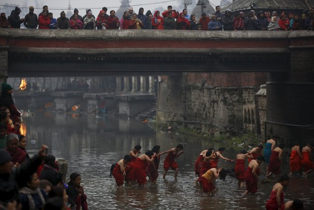 Devotees return after taking a holy bath at Bagmati River in Pashupatinath Temple during the Swastha