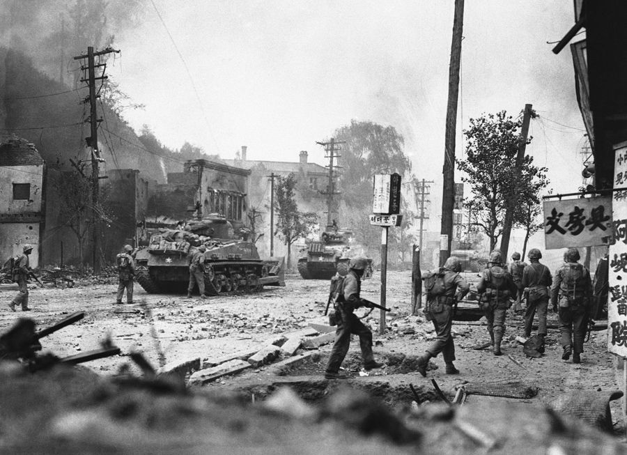 Rubble litters streets and smoke from burning buildings fills sky as tanks lead UN forces in the rec
