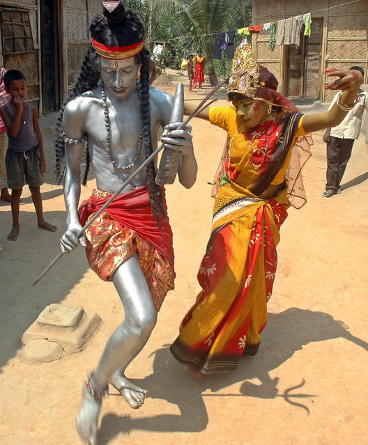 Artists dressed as Lord Shiva (L) and his wife Gauri perform in the street in Agartala March 31, 200