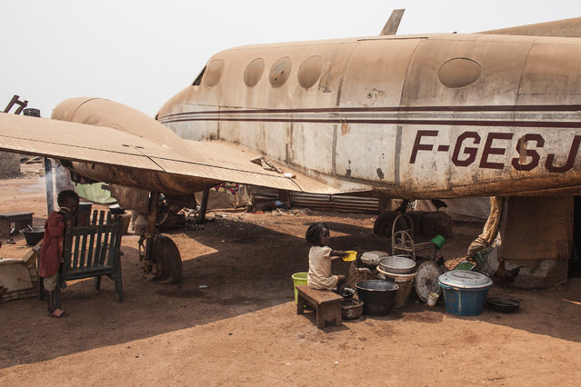 A girl washes dishes next to the wing of a plane wreckage being used as housing in M'Poko Inter