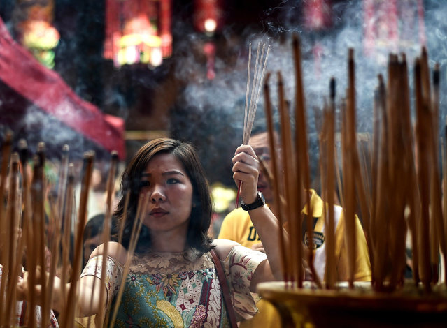 An ethnic Malaysian-Chinese devotee burns incense for good luck at the Guan Di Temple on the first d