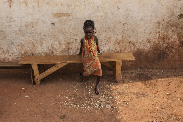A young girl sits on a bench in M'Poko Internally Displaced Persons camp in Bangui, Central Afr