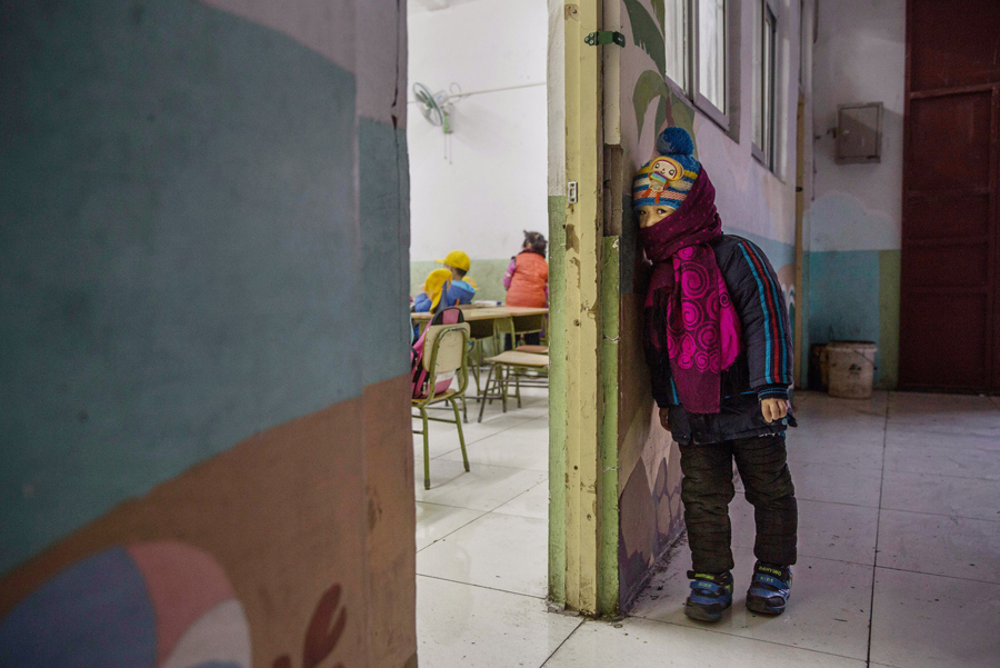 A Chinese student who is the child of migrants waits to enter class at an unofficial school on Decem