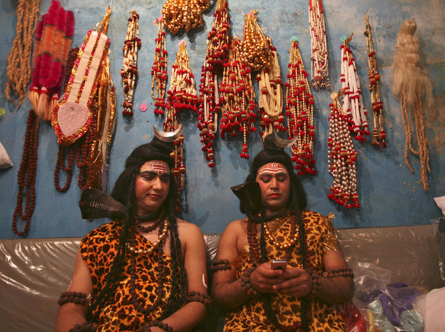 Artists dressed as Lord Shiva read a message on a mobile phone as they prepare to participate in a r