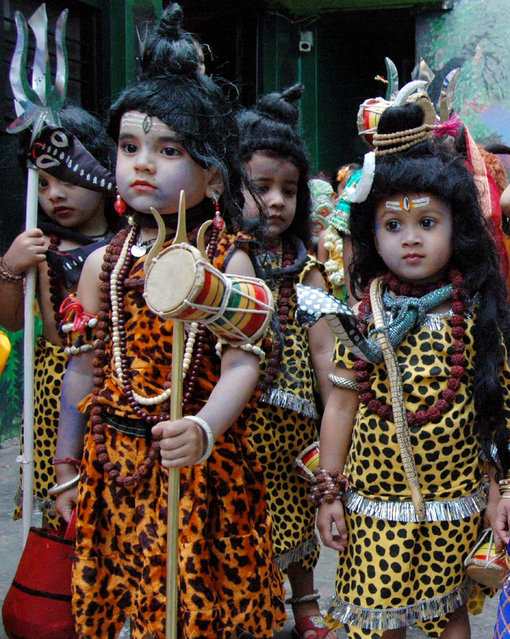 Children dressed as Lord Shiva take part in a religious procession on the eve of the Hindu festival