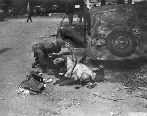 Американский санитар оказывает помощь лежащему у автомобиля  Opel Olympia 38 раненному немецкому офицеру. Нормандия, 1944 год.
