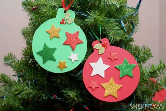 Сделайте шаблон елочного шара ивырежьте разноцветные шарики изплотной цветной бумаги или картона.