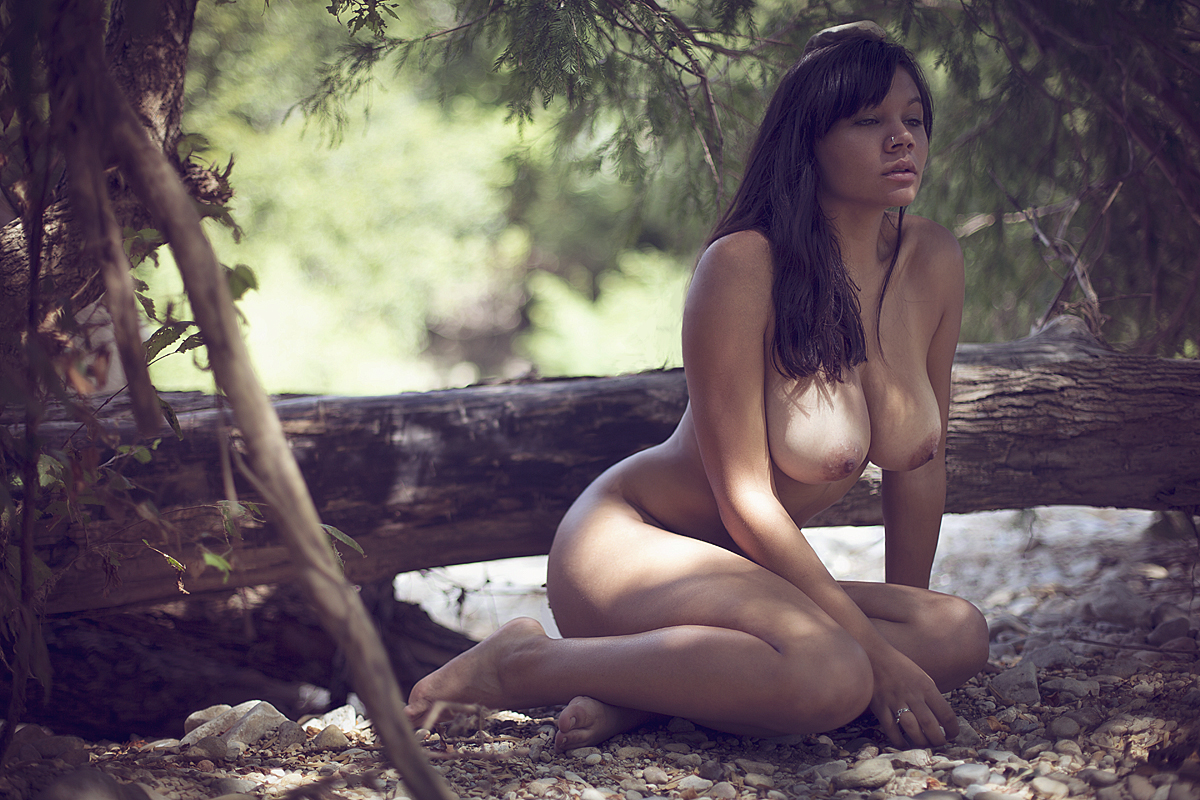 Photo of beautiful naked woman lying on a trunk of a tree in the nature black and white art nude