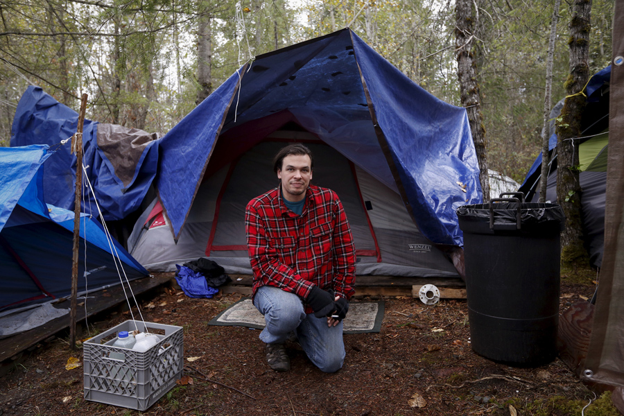 Stephan Schleicher, 31, poses in front of his tent at SHARE/WHEEL Tent City 4 outside Seattle, Washi