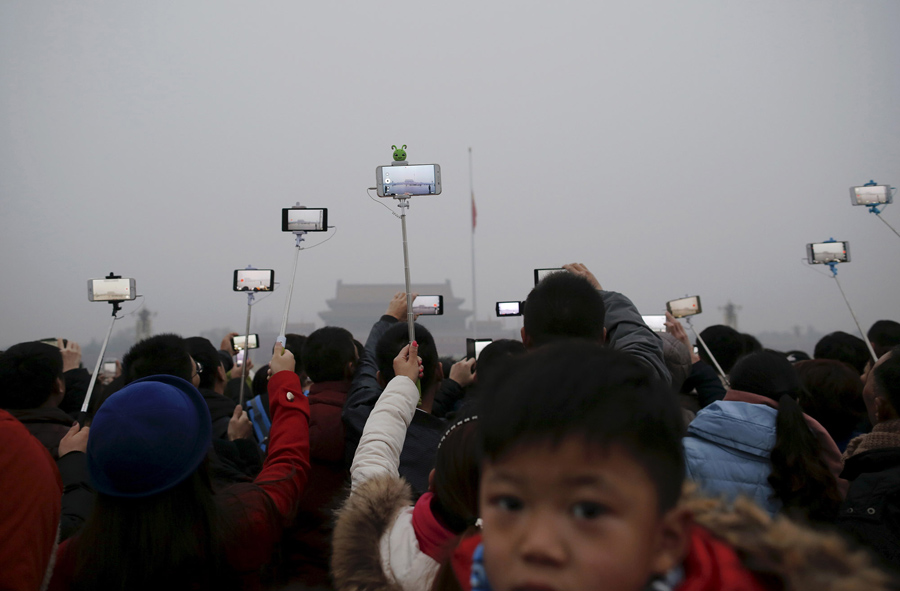 People take photos and videos during a flag-raising ceremony amid heavy smog at Tiananmen Square, af