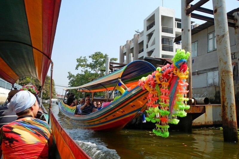Длиннохвостая лодка с гирляндами цветов на носу в каналах Бангкока