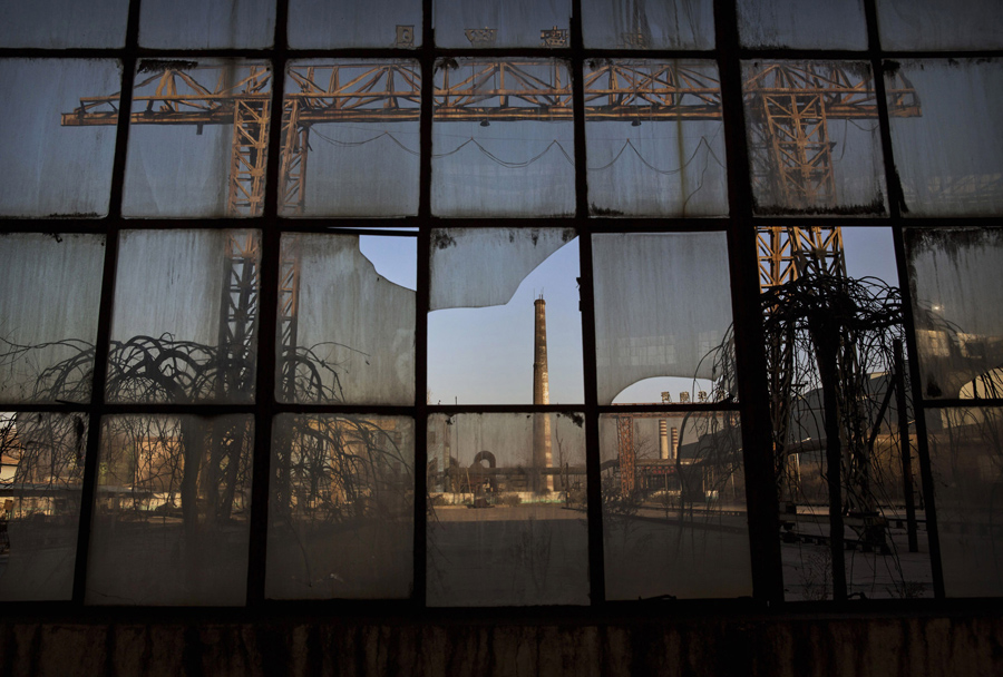 A smokestack is seen through a broken window of a building in the abandoned Qingquan Steel plant whi