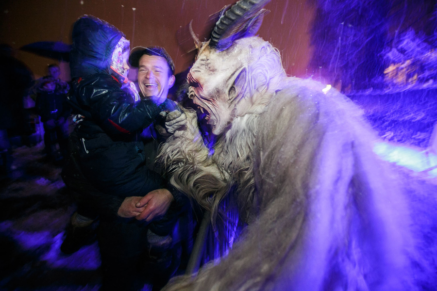 A participant dressed as the Krampus creature greets a child during the Krampus gathering in Gorican