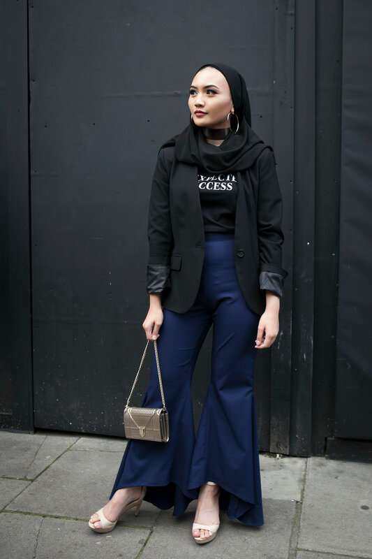 LONDON, ENGLAND - September 15, 2017 Beautiful and stylish woman in black scarf posing during the London Fashion Week. outside Eudon Choi