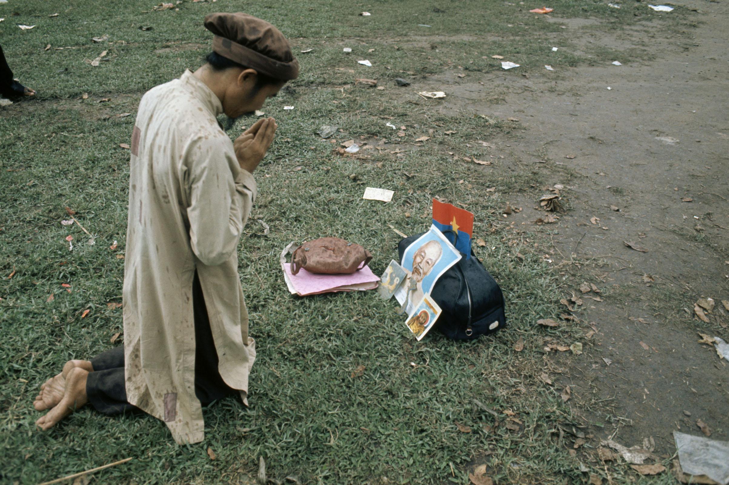 Вьетнамец молится перед портретом Хо Ши Мина после падения Сайгона. 30 апреля 1975