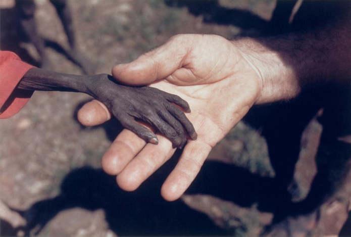 Сильно исхудавшая рука мальчика лежит в руке католического монаха в регионе Карамоджа северо-восточн