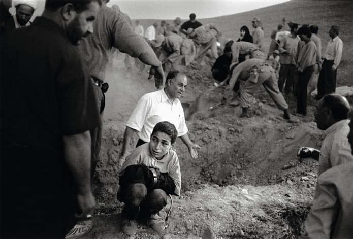 Казвин, Иран. Мальчик держит брюки своего мертвого отца, сидя на корточках рядом с местом, где его о