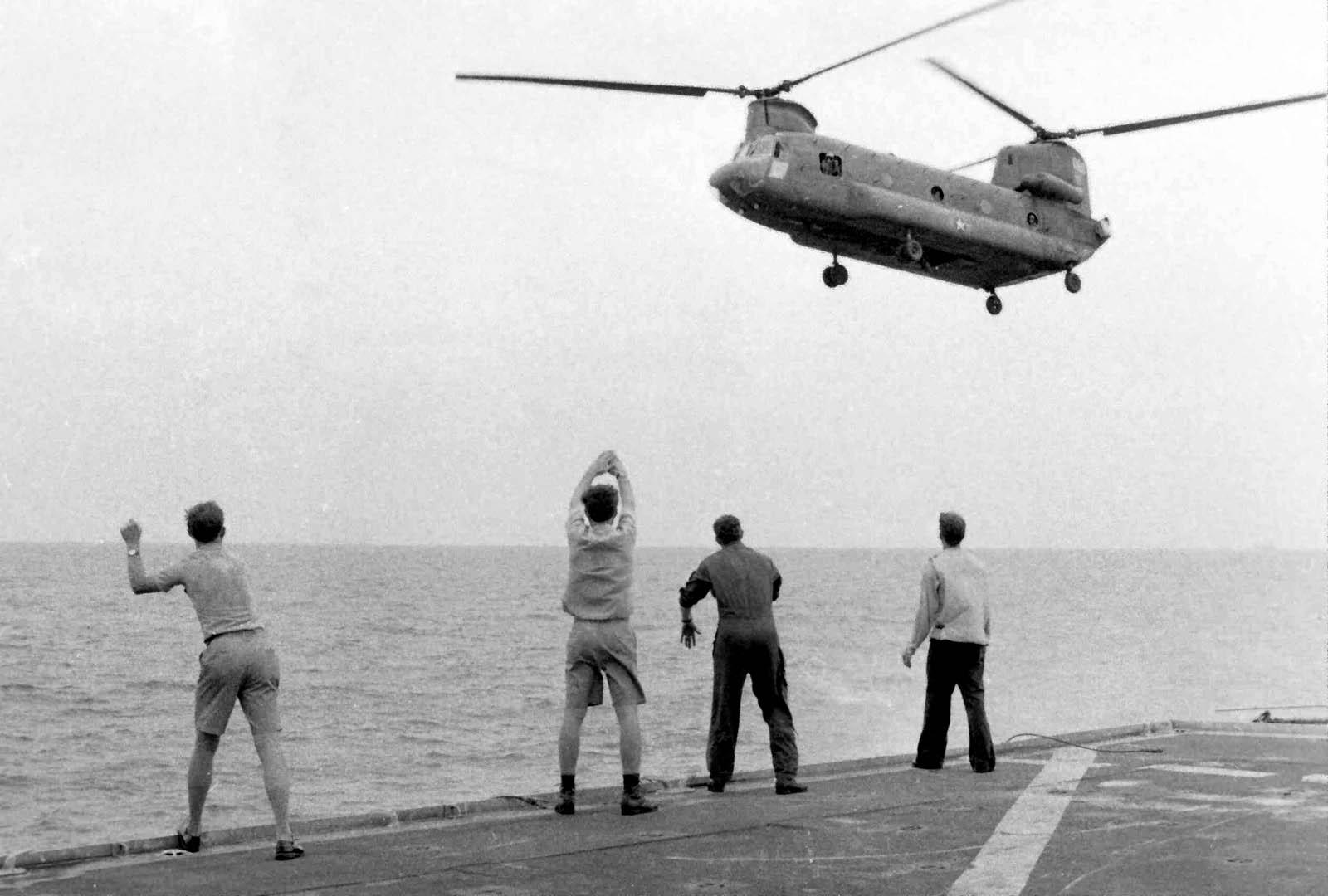 На борту USS Kirk члены экипажа сигнализируют, что Боинг CH-47 «Чинук» парит над палубой и может высаживать пассажиров. 29 апреля 1975