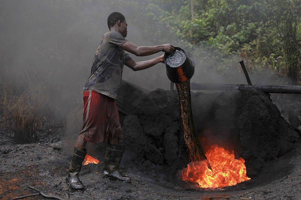 Разлитую по округе нефть из незаконной врезки около реки Нун черпают ведрами, 27 ноября 2012.