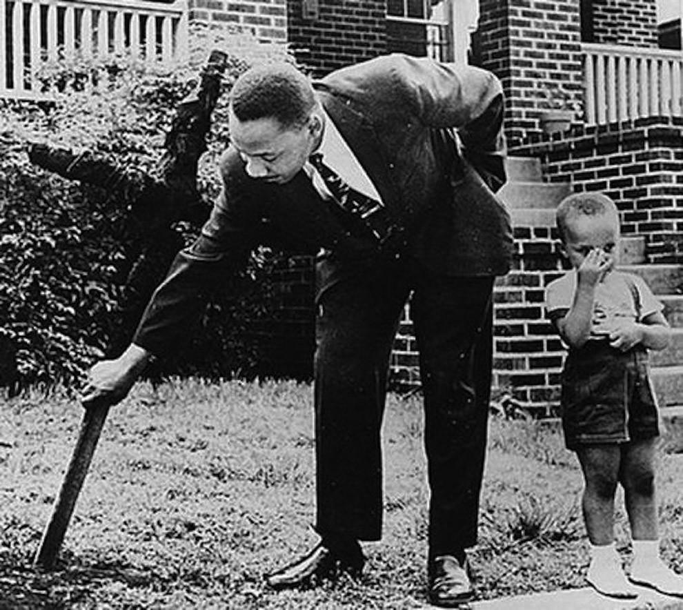 24. Мартин Лютер Кинг и его сын убирают сожженный крест с лужайки своего дома, 1960 год.