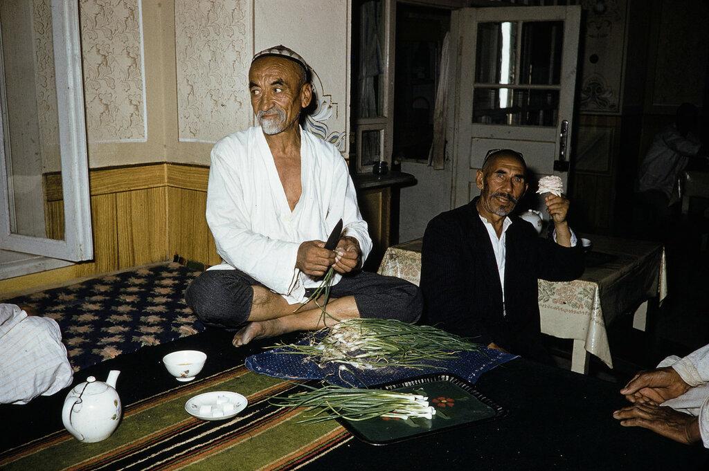 Uzbekistan, man trimming green onions in Samarkand tea shop