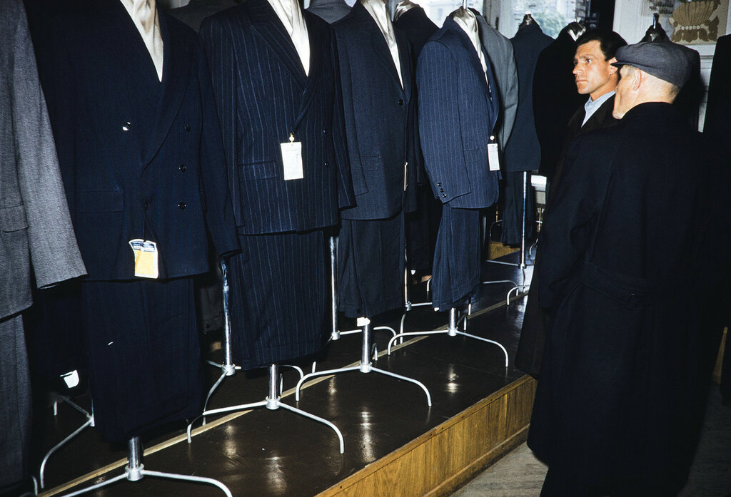 Russia, men looking at suit display at store in Moscow