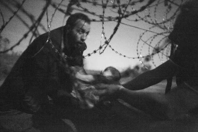 Ребенка передают через отверстие в ограждении из колючей проволоки сирийскому беженцу, которому уже