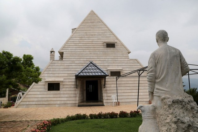 A statue is pictured in front of a pyramid house in the village of Miziara, northern Lebanon. Photo
