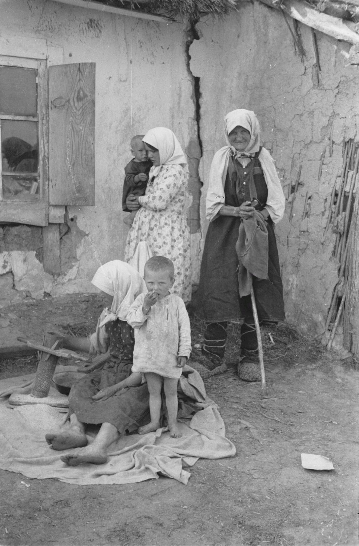 Группа женщин и детей перед крестьянской избой