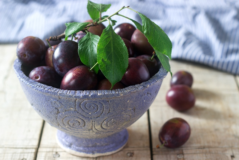 Plums in a clay bowl on a wooden table. Rustic style, selective focus.