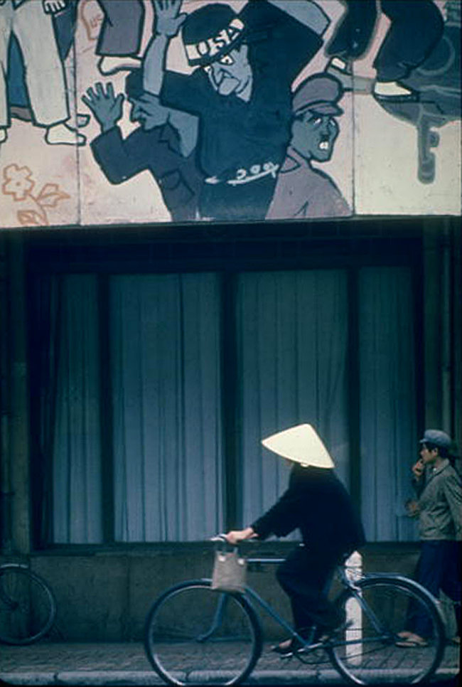 Велосипедист проезжает мимо огромного плаката. Плакат изображает президента Джонсона в компании с Гитлером
