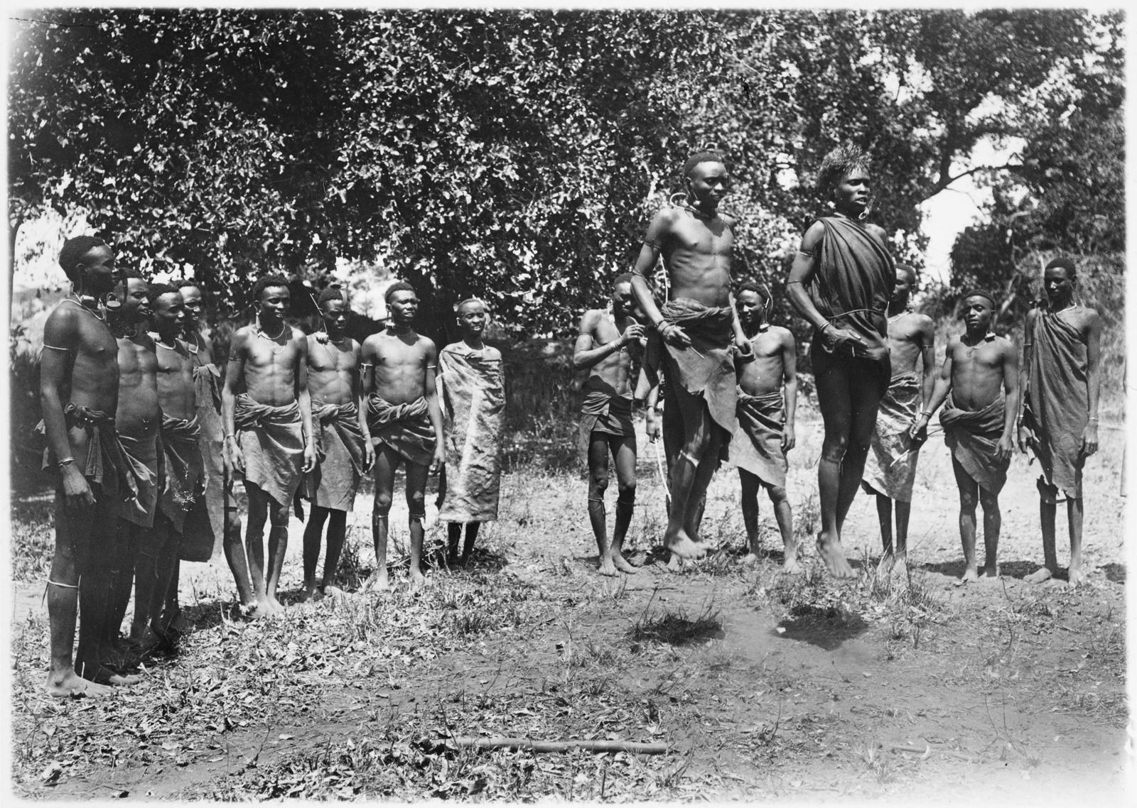 04. Группа людей басонжо во время танца у лагеря Ндалалани. Танцоры прыгают на два фута высотой, вытянув тела